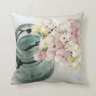 Flores rosadas y amarillas en tarro del azul del almohada