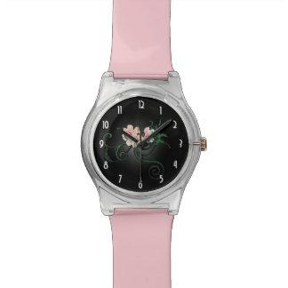 Flores rosados de la flor en un fondo negro relojes de mano