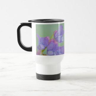 Flores salvajes púrpuras suaves con un fondo verde taza térmica