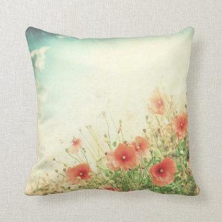 Flores salvajes rosadas en almohada del sofá del