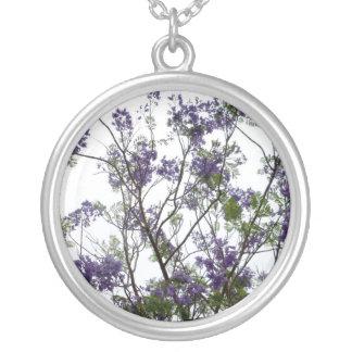 flores verdes púrpuras contra el cielo brillante f colgante redondo