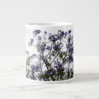 flores verdes púrpuras contra el cielo brillante f taza grande