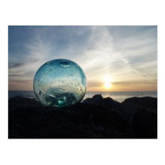 Flotador de cristal y puesta del sol tarjeta postal