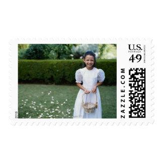Flower girl (4-7) holding basket of petals, postage