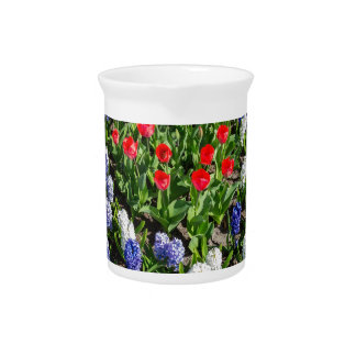 Flowers field with red blue tulips and hyacinths drink pitcher