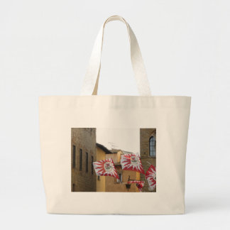 Fluttering flags in Volterra village . Tuscany Large Tote Bag