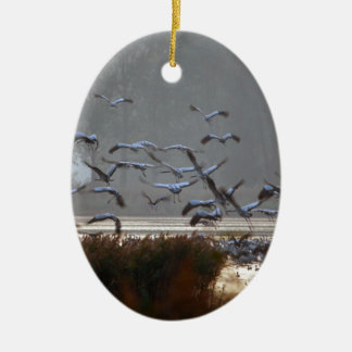 Flying cranes on a lake ceramic ornament