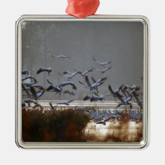 Flying cranes on a lake metal ornament