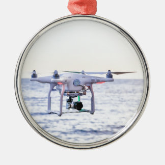 Flying drone at coast above sea metal ornament