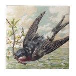 "Flying swallow with more flower twig ceramic tile<br><div class=""desc"">Novel TIC vintage picture OF A flying swallow with A blossoming twig,  with the sea underneath.</div>"