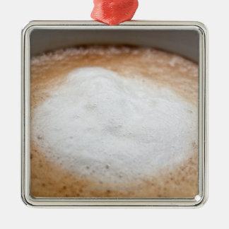 Foam on cappuccino, close-up metal ornament