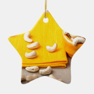 Foco selectivo en el mantel y el anacardo crudo adorno navideño de cerámica en forma de estrella