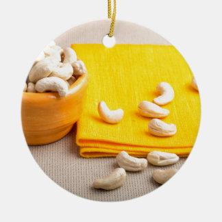 Foco selectivo en el mantel y el anacardo crudo adorno navideño redondo de cerámica