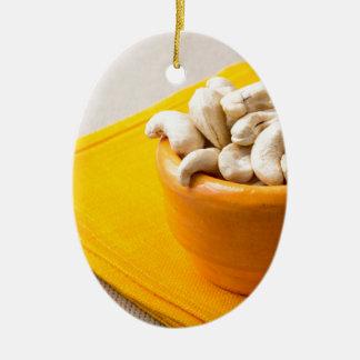 Foco selectivo en los anacardos crudos en una adorno navideño ovalado de cerámica