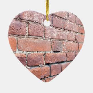 Foco selectivo en una pared de ladrillo en ángulo adorno navideño de cerámica en forma de corazón