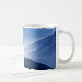 Fog covered mountain silhouettes coffee mug