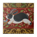 """Folk Rabbit Tile<br><div class=""""desc"""">Get this modern piece of artwork today with a brown and red background. This piece of art contains a black and white rabbit which appears to be running. The details in this image are very sharp and vivid. It&#39;s a contemporary art piece that will be perfect for any type of...</div>"""