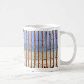 fondo de la playa de la cerca del torno de la taza básica blanca