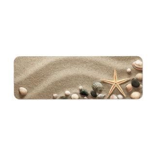 Fondo de la playa de Sandy con las cáscaras y las  Etiqueta De Remite