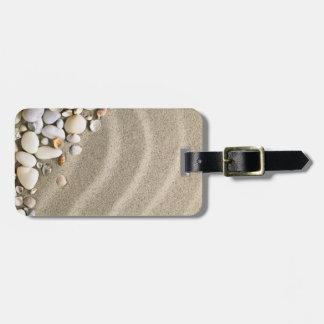 Fondo de la playa de Sandy con las cáscaras y las  Etiquetas Maletas