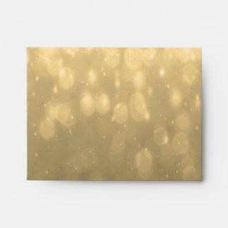 Fondo - luces del brillo de Bokeh del oro Sobres