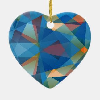 Fondo polivinílico bajo azul anaranjado adorno navideño de cerámica en forma de corazón