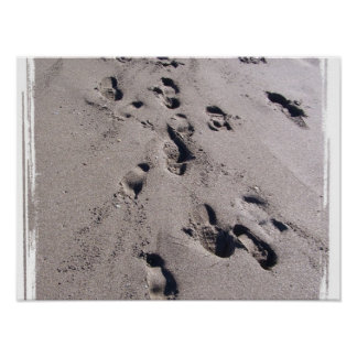 Foot prints in wet beach sand towards viewer poster