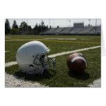 Football and football helmet on football field greeting cards