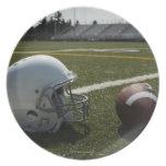 Football and football helmet on football field dinner plates