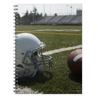 Football and football helmet on football field notebook