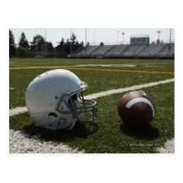 Football and football helmet on football field postcard
