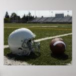 Football and football helmet on football field poster