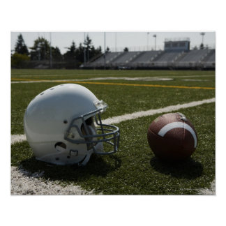 Football and football helmet on football field poster