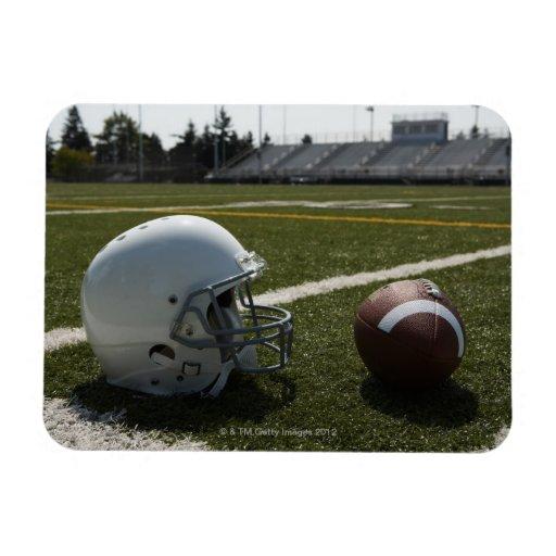 Football and football helmet on football field vinyl magnet