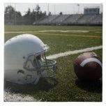 Football and football helmet on football field tile