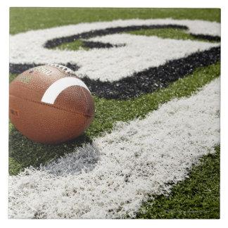 Football at goal line on football field, ceramic tile