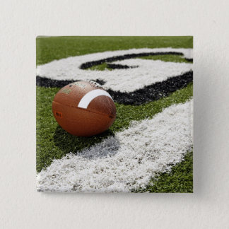 Football at goal line on football field, pinback button