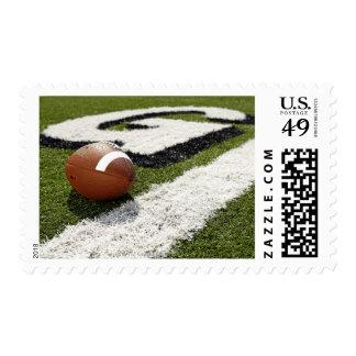 Football at goal line on football field, postage