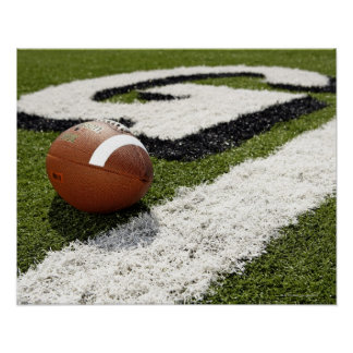 Football at goal line on football field, poster