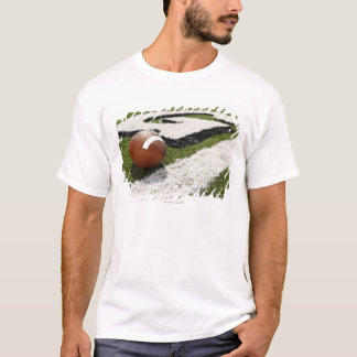Football at goal line on football field, T-Shirt