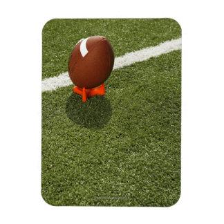 Football atop tee on football field, elevated magnet