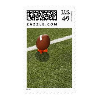 Football atop tee on football field, elevated postage stamp