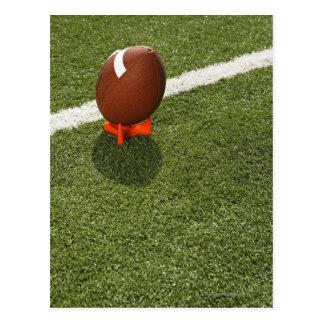 Football atop tee on football field, elevated postcard