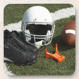Football, football helmet, tee and shoes on beverage coaster