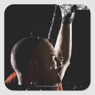 Football player cooling off with water square sticker