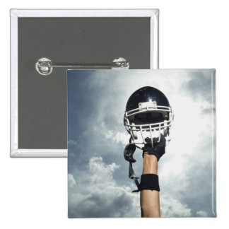 Football player holding helmet in air 2 inch square button