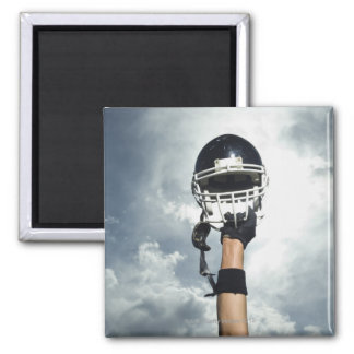 Football player holding helmet in air 2 inch square magnet
