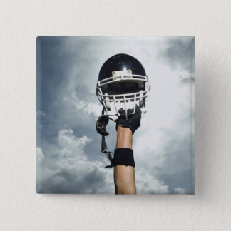 Football player holding helmet in air button