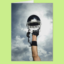 Football player holding helmet in air card