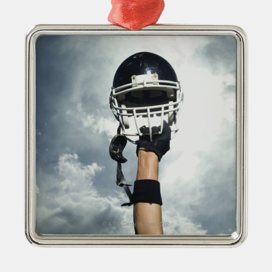 Football player holding helmet in air metal ornament